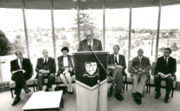 This image is showing Mr W. [Bill] Gribble giving a speach and Joan Kirner Premier of Victoria, Mr E.J.[Jack] Barker, ? sitting behind him in the reading room inside the E.J.Tippett Library